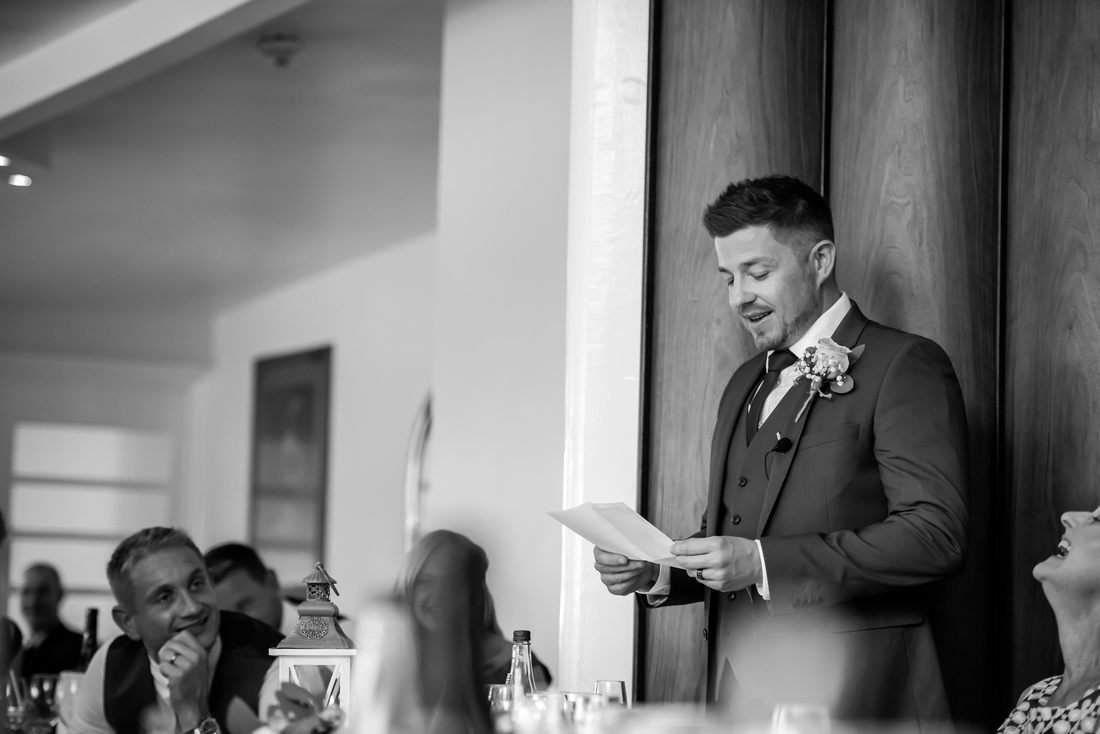 Black and white image of the best man giving his speech, from a wedding at Portmeirion.