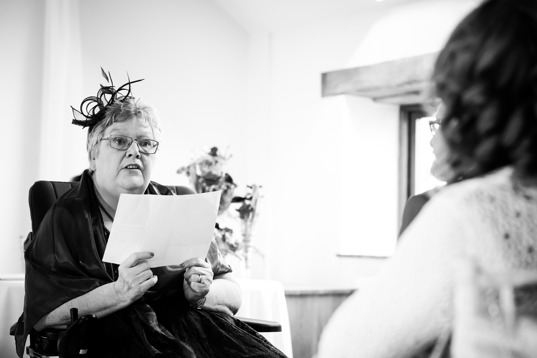 Black and white photo of the groom's mum doing a reading during the wedding ceremony at Beeston Manor.