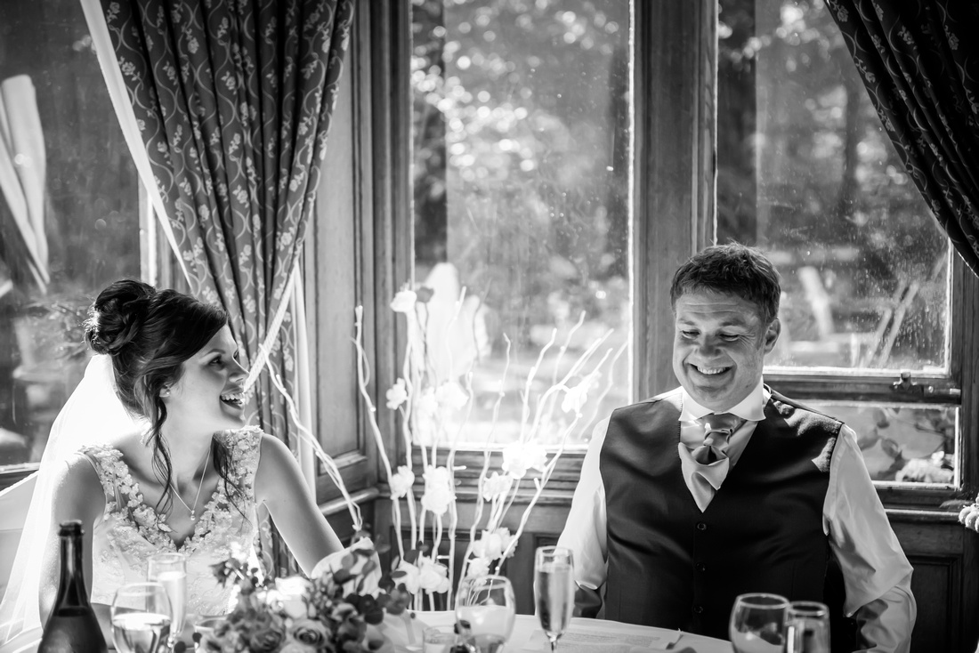 Black and white image of bride glancing at her father during the speeches at her wedding at Ruthin Castle.