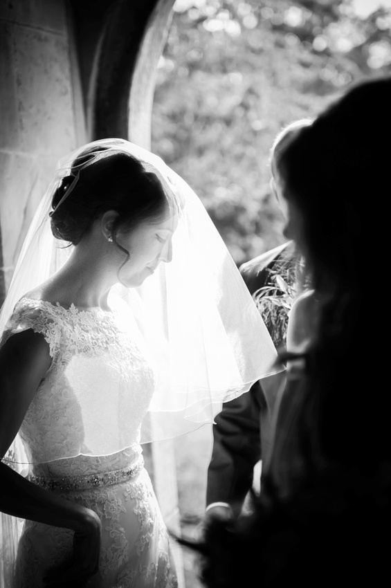 Bride in Doorway of Church with her Veil Down by North Wales Wedding Photographer Celynnen Photography
