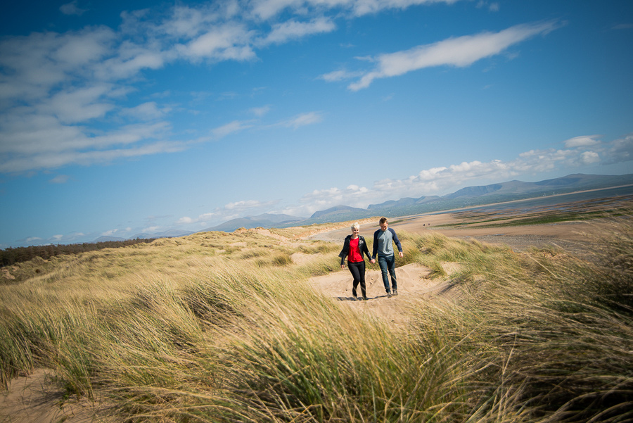 Photograph of Liz & Jason walking through the sand dunes, holding hands.  Photographed by Celynnen Photography.