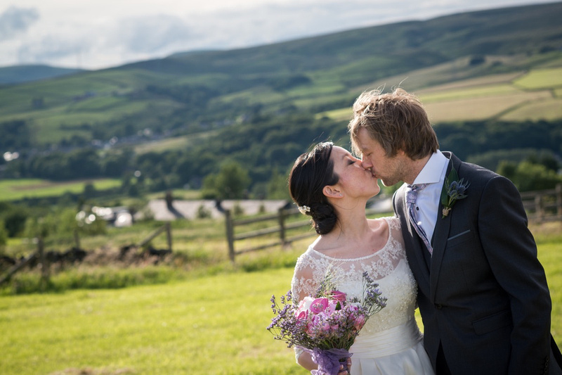 Bride and groom kissing with North Wales scenery in the background.