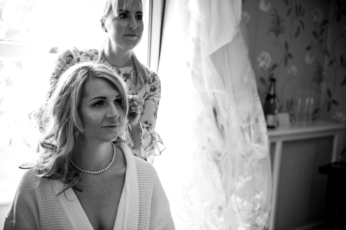 Bride having makeup done as she's getting ready in Portmeirion Hotel for her wedding.