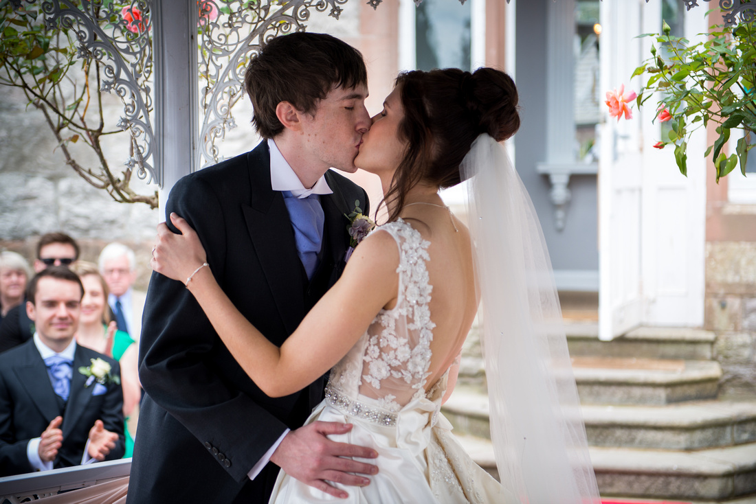 Photo of the bride and groom's first kiss as a married couple. Photo taken during ceremony at Ruthin Castle.