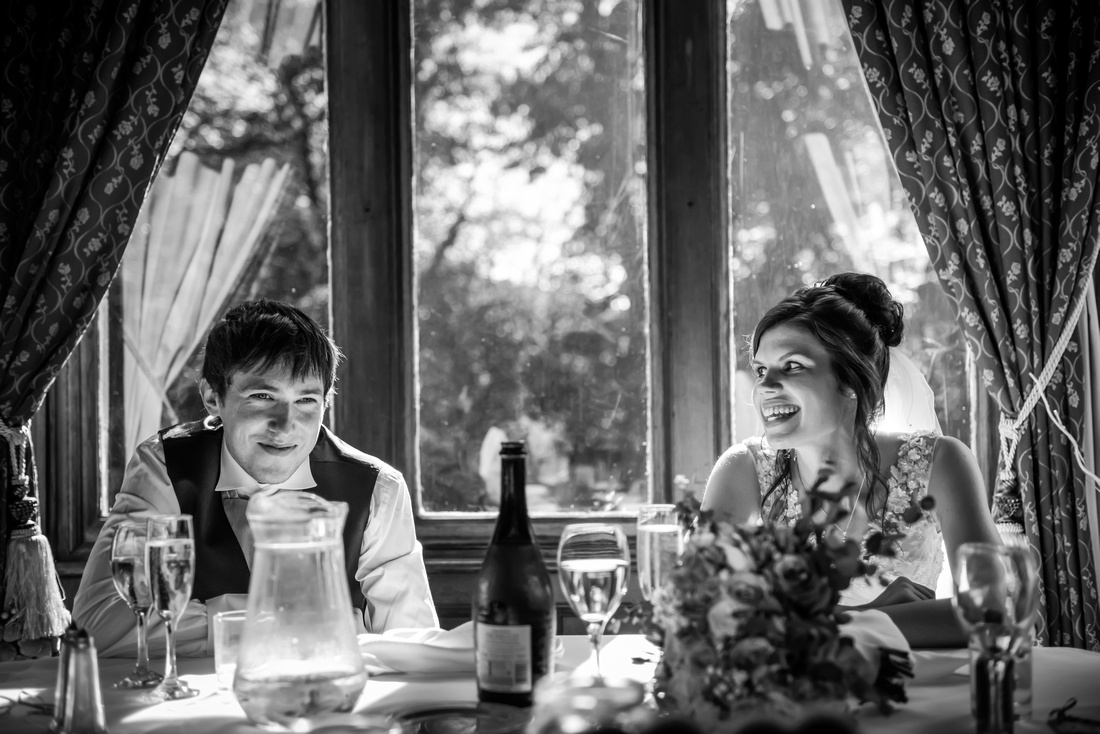 Black and white picture of the bride glancing at her groom during the speeches of her wedding day at Ruthin Castle.
