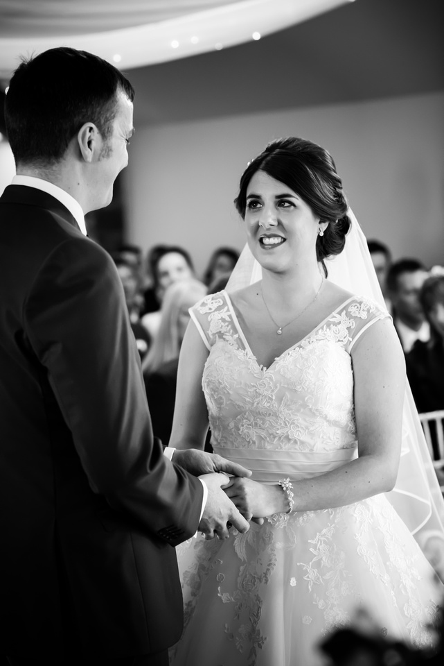 Black and white photo of the bride and groom during the vows of their wedding ceremony at Beeston Manor.