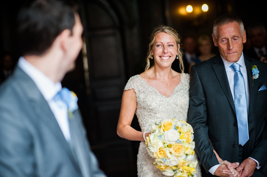 Bride smiling as she sees her husband to be at their wedding in Portmeirion. Wedding photographer, Celynnen Photography