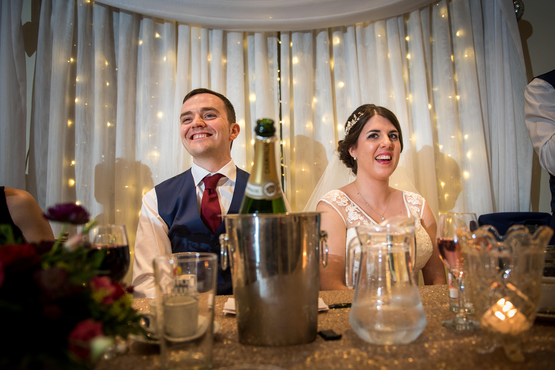 Photo of the bride and groom enjoying the speeches at their wedding at Beeston Manor.