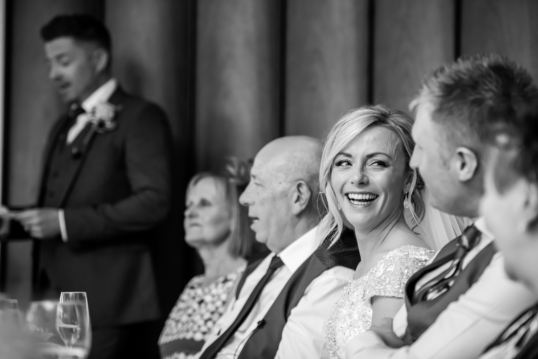 Black and white image of the bride gazing back at her groom during the best man's speech. From a wedding at Portmeirion.