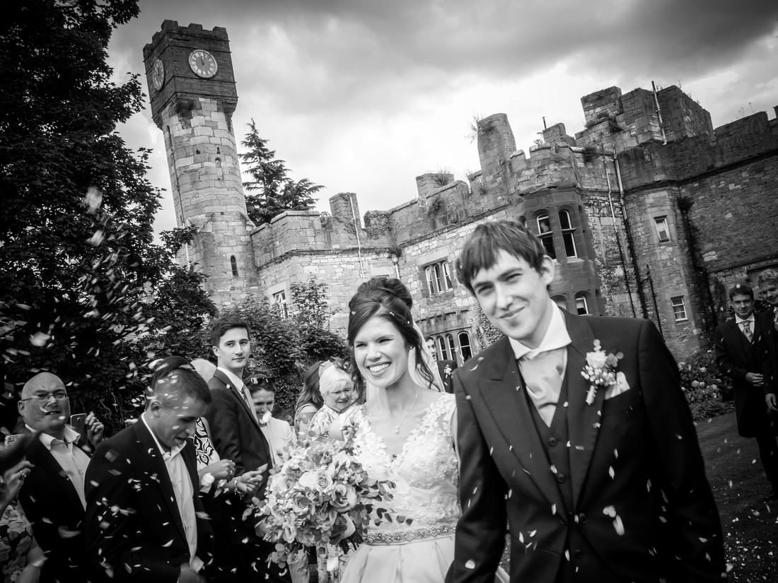 Black and white image of bride and groom being showered with confetti at Ruthin Castle.