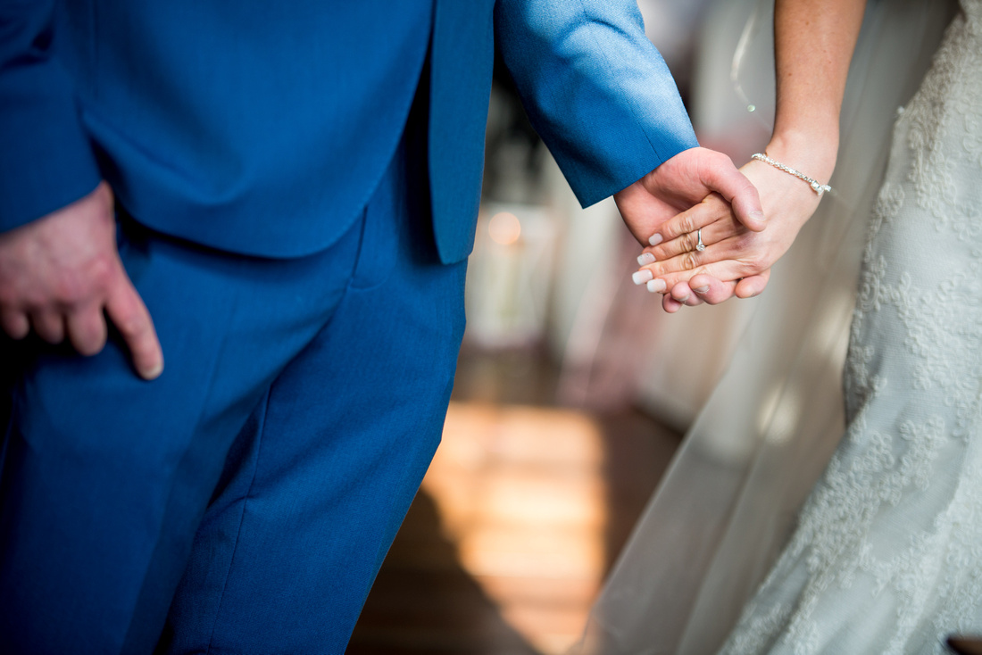 Photo of the groom and bride holding each others hand during the wedding ceremony at Portmeirion.