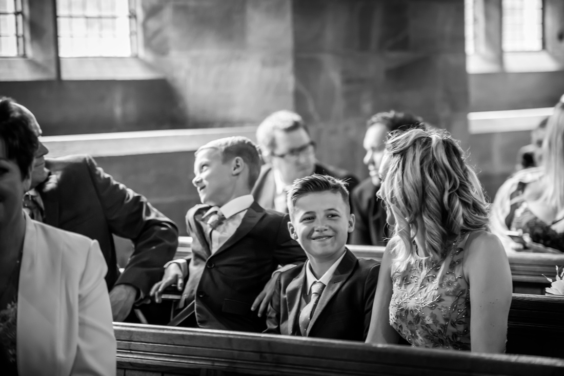 Black and white image of guests waiting for the wedding ceremony at a church in Halkyn.