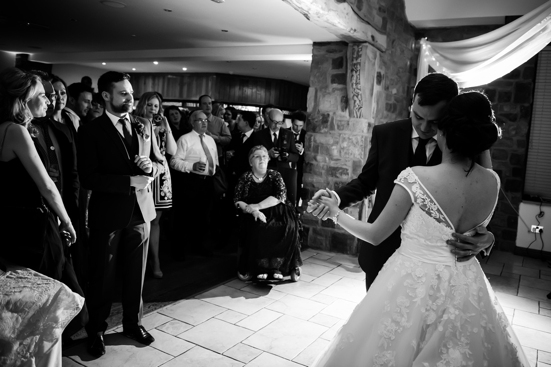 Black and white image of everyone watching the bride and groom's first dance as a married couple at a wedding at Beeston Manor.