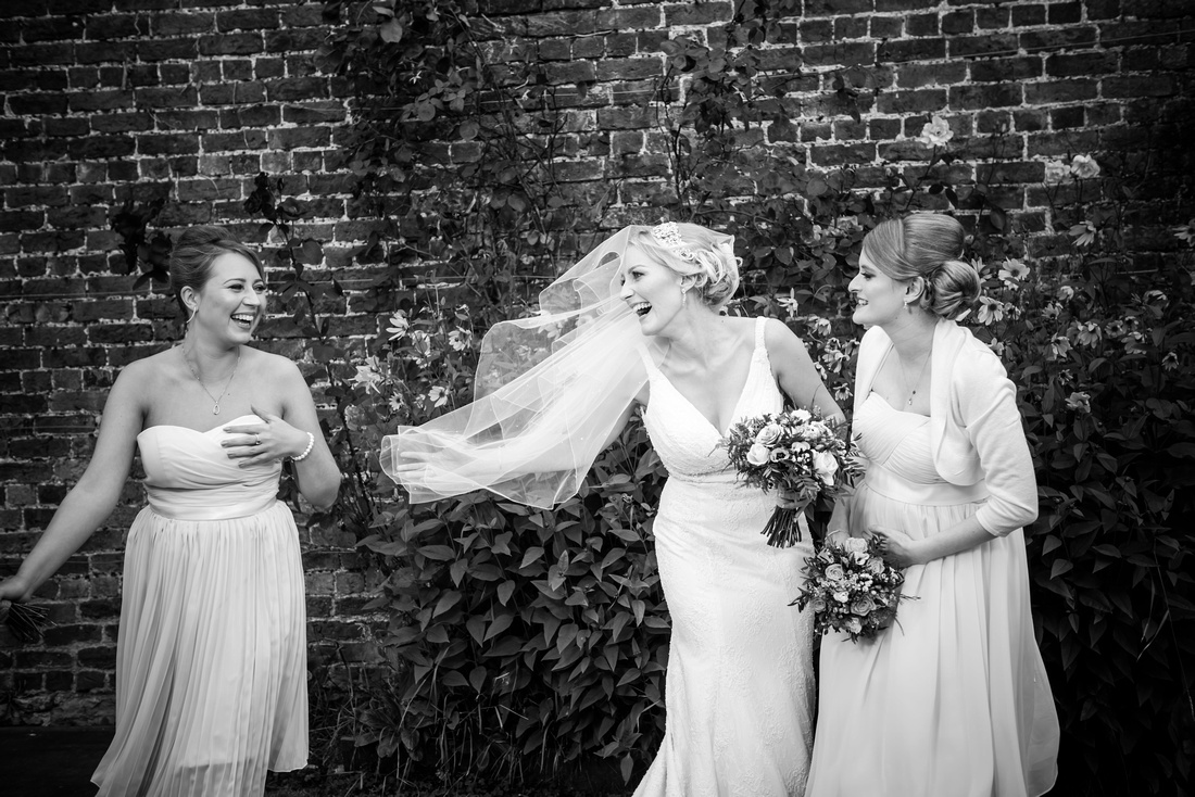 Black and white image of the bride laughing with her bridesmaids on her wedding day at Pentre Mawr.
