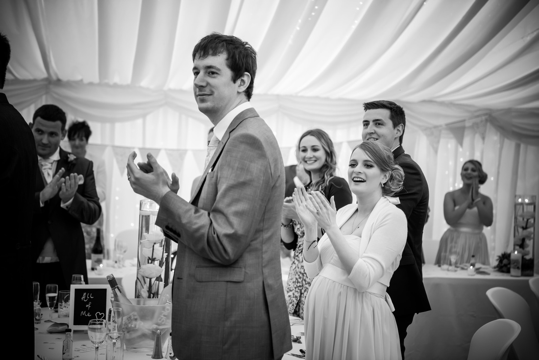 Black and white image of the guests applauding the bride and grooms entrance for the reception at Pentre Mawr.