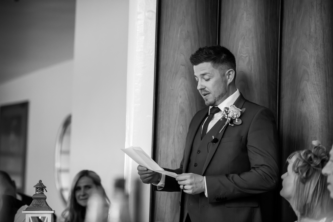 Black and white image of the best man giving his speech at a wedding in Portmeirion.