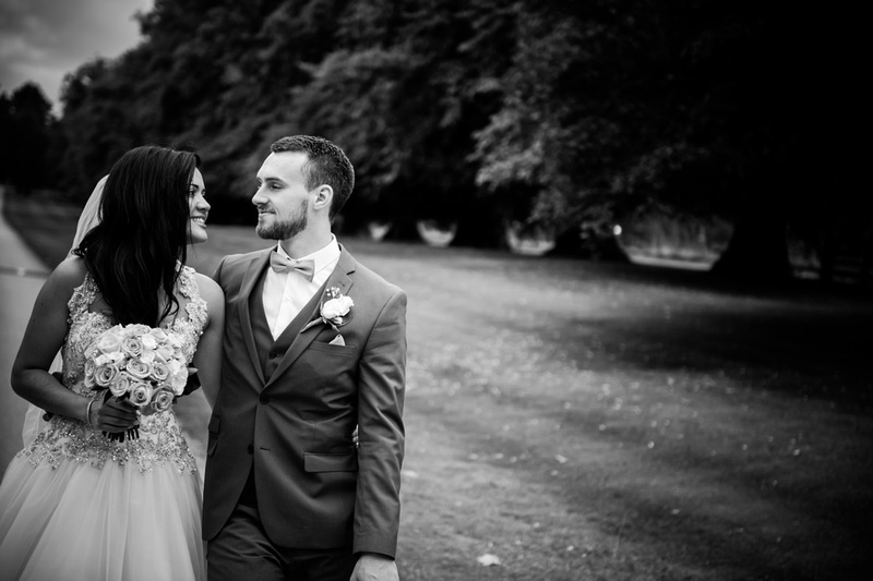 Black and white image of the bride and groom walking around the grounds of Soughton Hall.