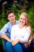 Couple sitting together for a portrait in their pre wedding photoshoot in Newborough Forest