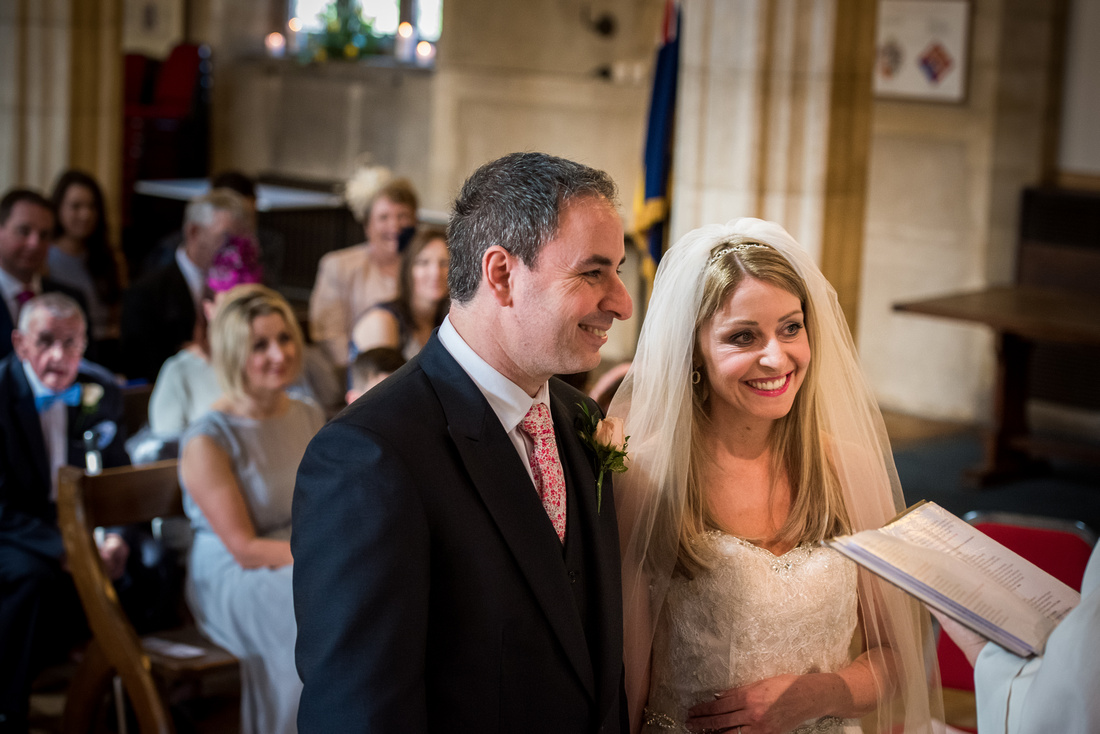 Image of the bride and groom looking happy during their wedding ceremony in Buckinghamshire.