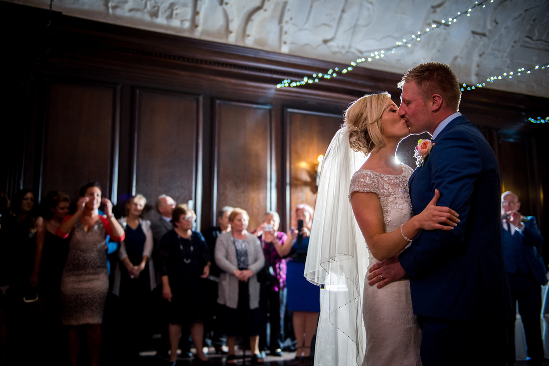 Picture of bride and groom sharing a kiss after their first dance as a married couple. Wedding at Portmeirion.