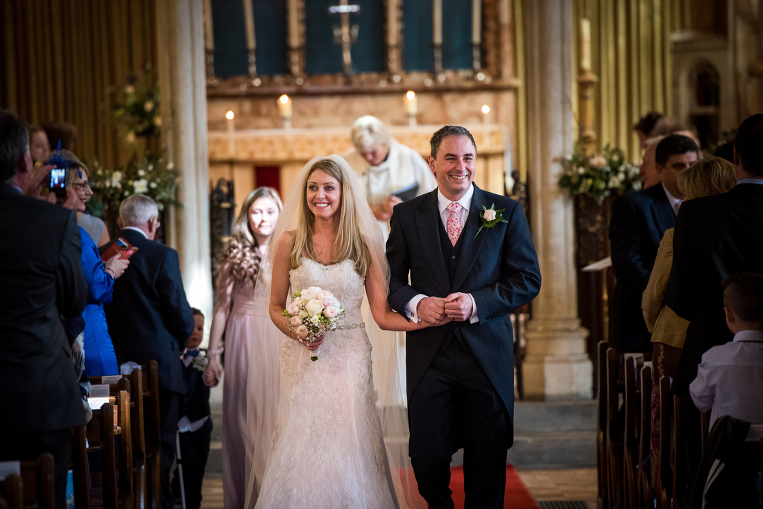 Image of the bride and groom leaving their wedding ceremony as husband and wife, in Buckinghamshire.