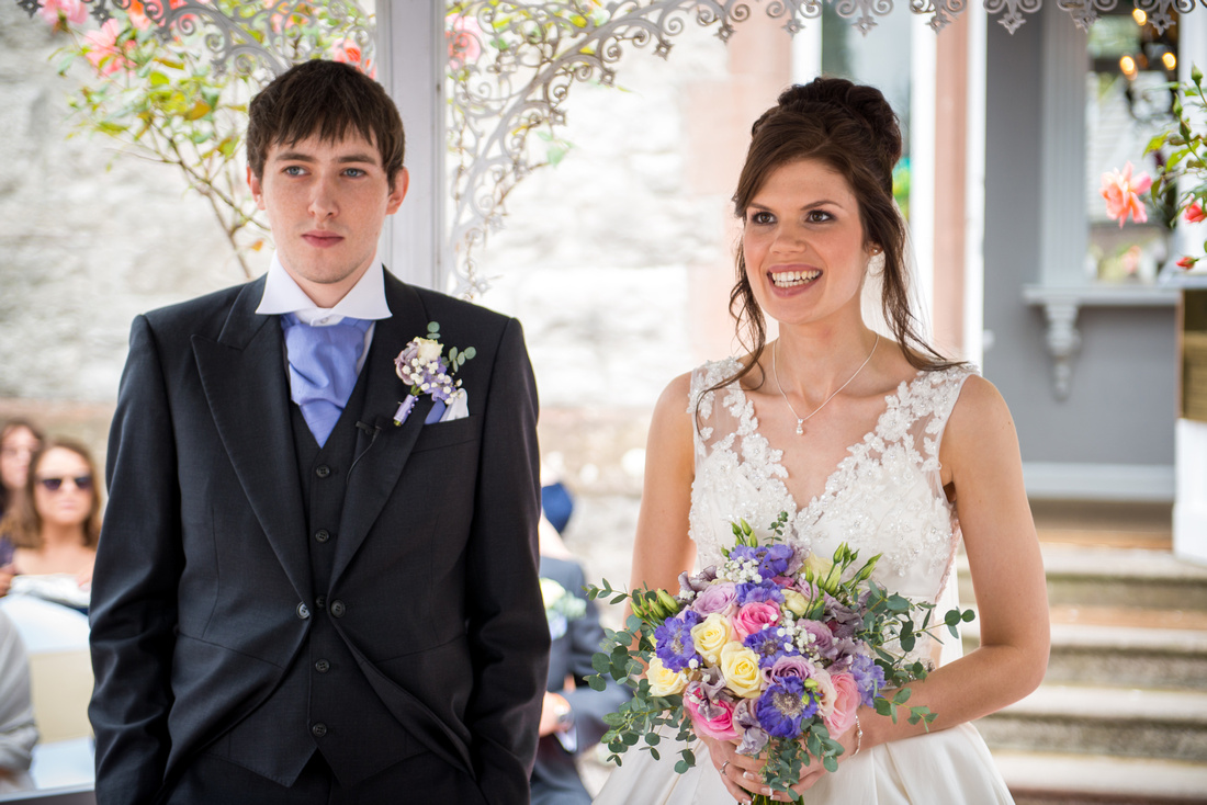 Colour photo of the bride and groom during their wedding ceremony at Ruthin Castle.