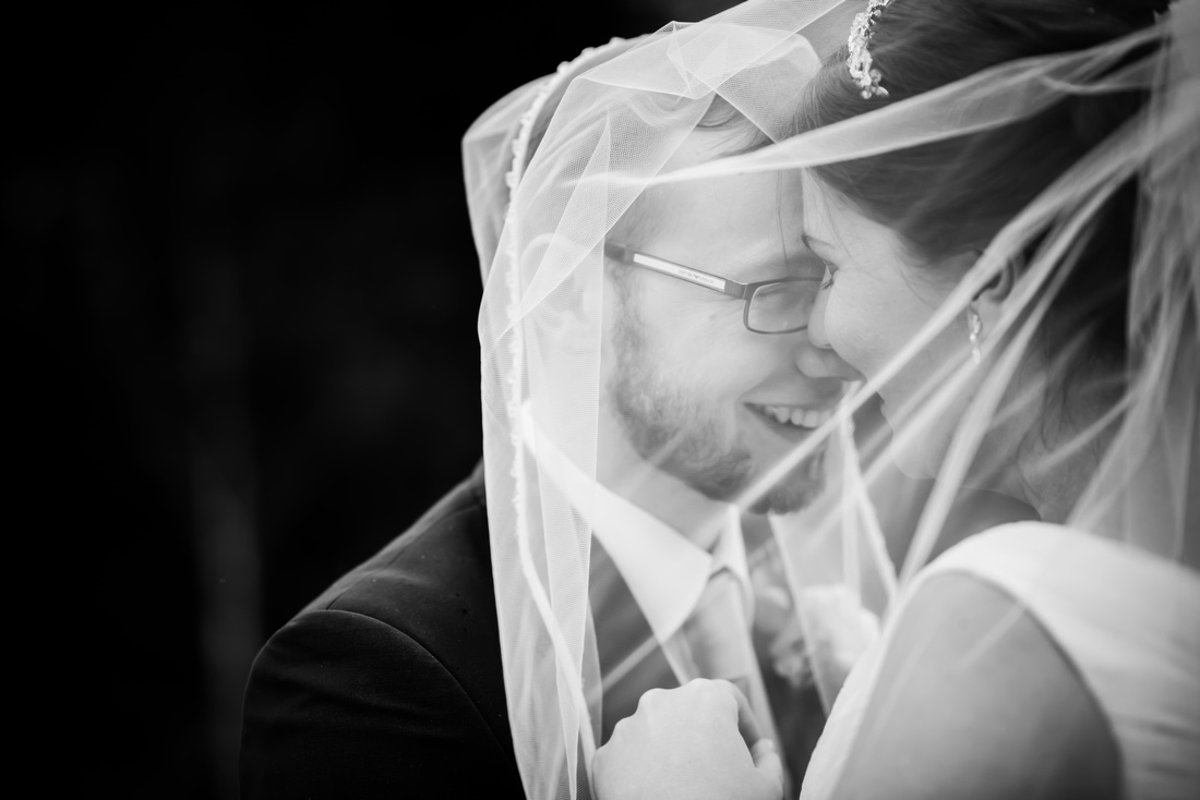 Black and white image of the bride and groom embracing each other under the bride's vale at a wedding at Mere Brook House.