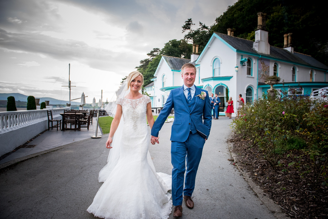 Picture of bride and groom walking around the scenic surroundings of Portmeirion on their wedding day.