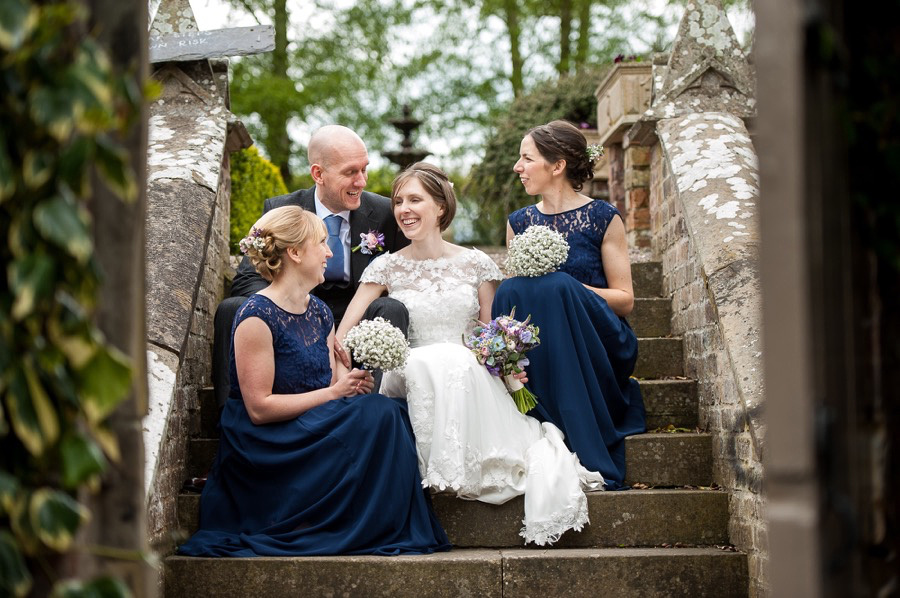 A photograph of Ross & Mair with their bridesmaids sitting on the steps at Soughton Hall