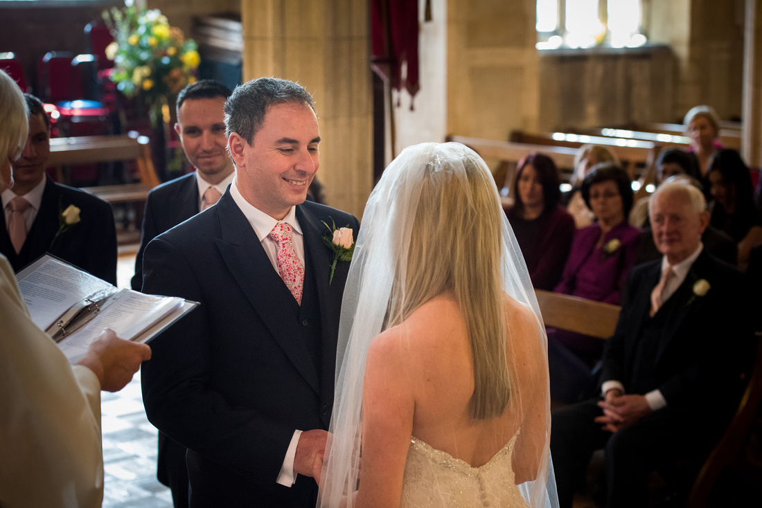 Image of the groom smiling at the bride during their wedding ceremony in a church in Buckinghamshire.