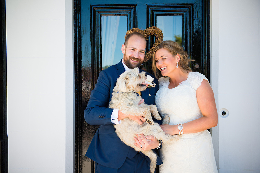 Bride and groom having a photo with their dog on their wedding day in Anglesey.