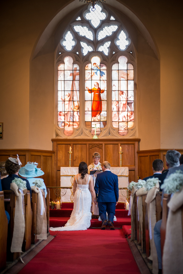 Image from the back of the church showing the bride and groom in front of a stain glad window in a church in Llandegla during their wedding ceremony.
