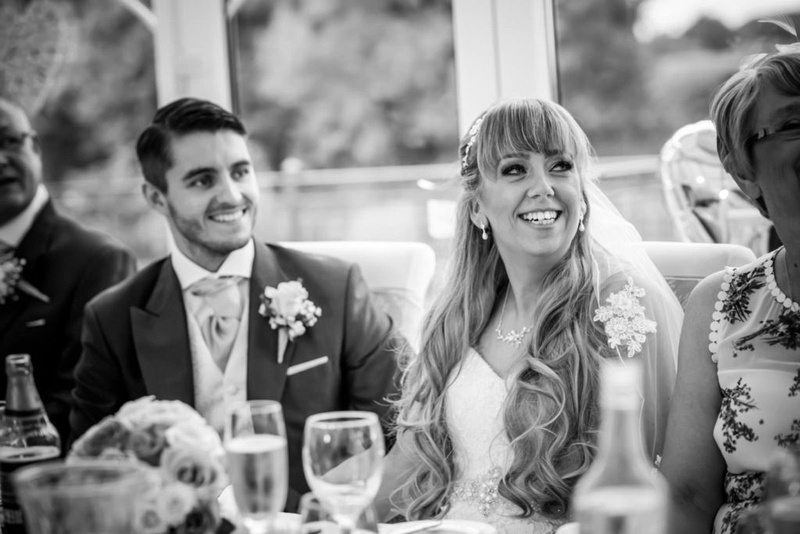 Bride smiling in the direction of her father during the speeches at her wedding at the Lion Quays.