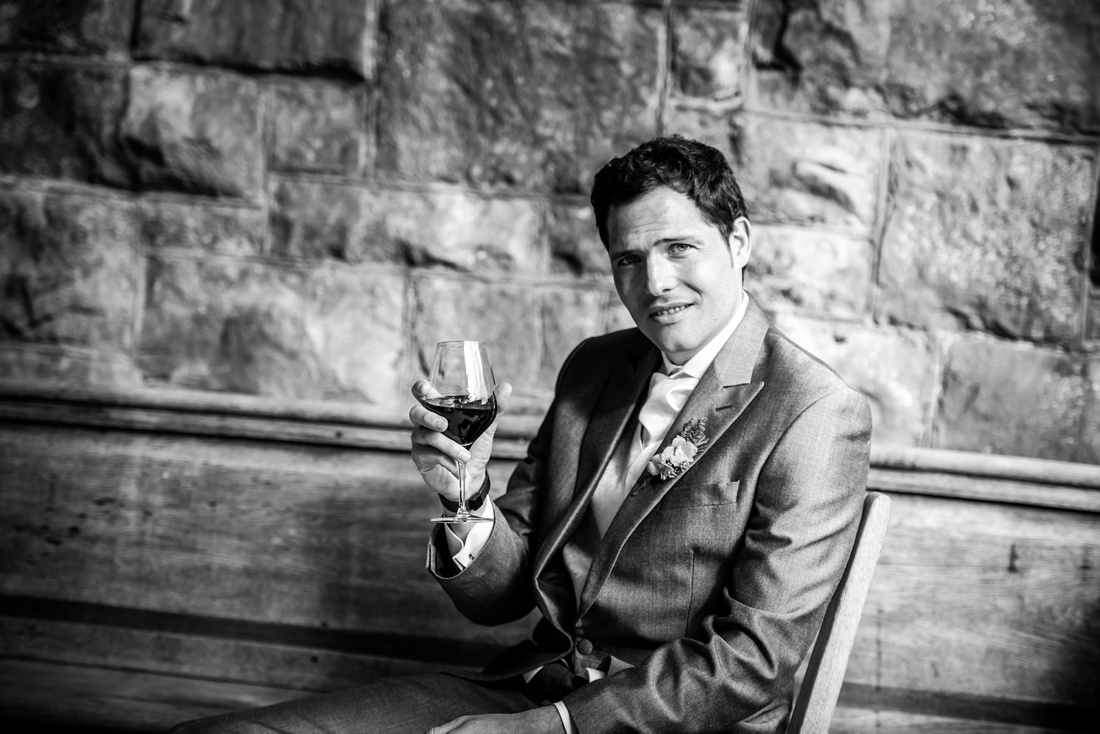 Black and white image of the groom enjoying a glass of wine on his wedding day at Tower Hill Barns.