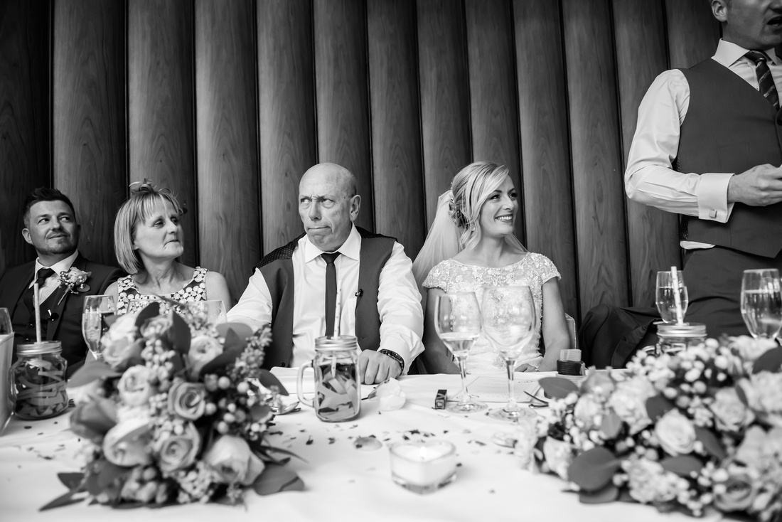 Black and white photograph of the father of the bride pulling a funny face during the groom's speech at a wedding in Portmeirion.