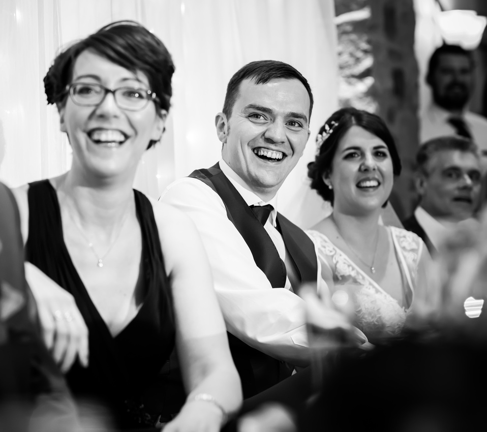 Black and white image of the groom really enjoying the speeches at his wedding at Beeston Manor.