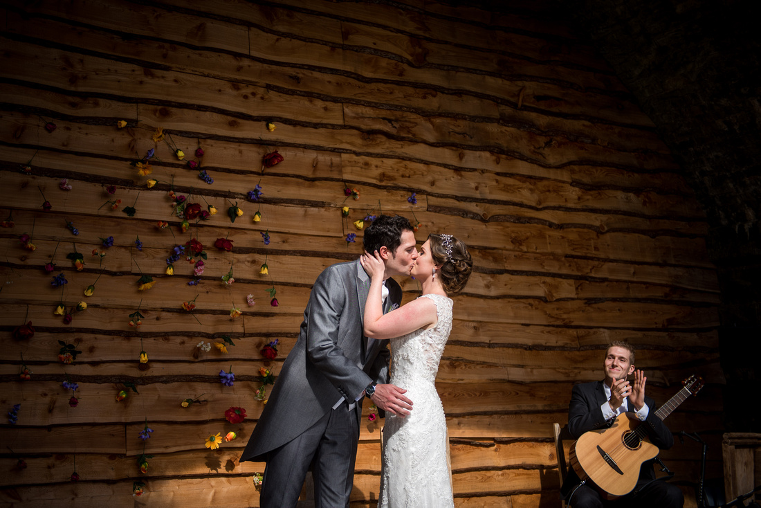 Image of the bride and groom sharing their first kiss as a married couple during their wedding ceremony at Tower Hill Barns.