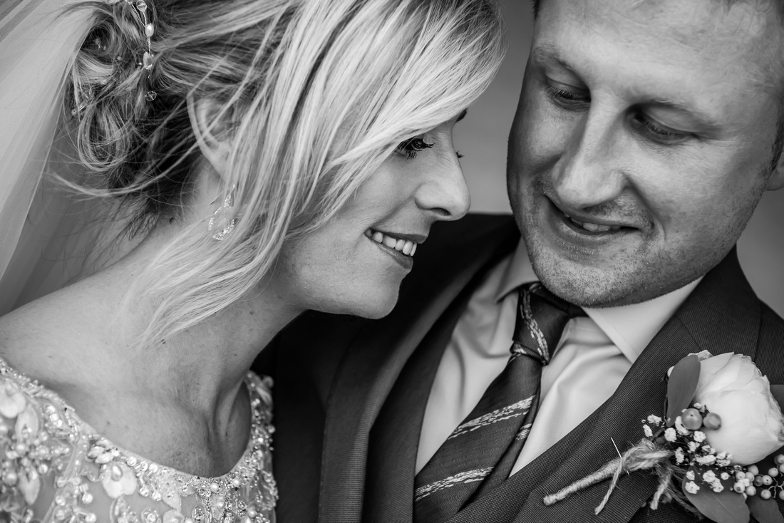 Black and white image of the bride and groom getting close on the wedding day at Portmeirion.