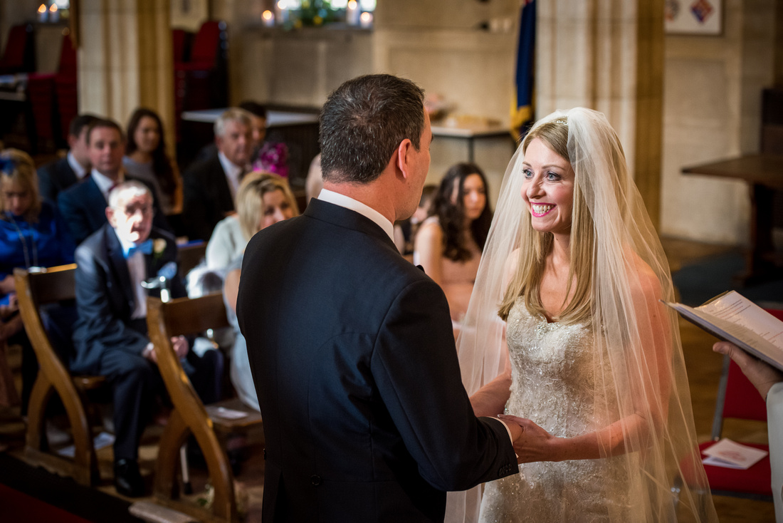 Image of the bride smiling at the groom during their wedding ceremony in a church in Buckinghamshire.