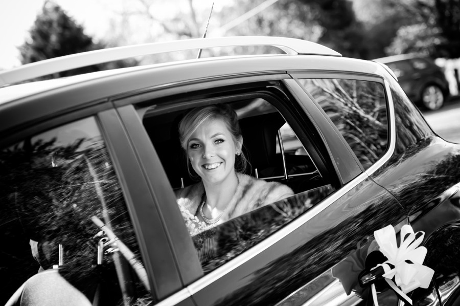 Bride smiling in wedding car by North Wales Wedding Photographer Celynnen Photography
