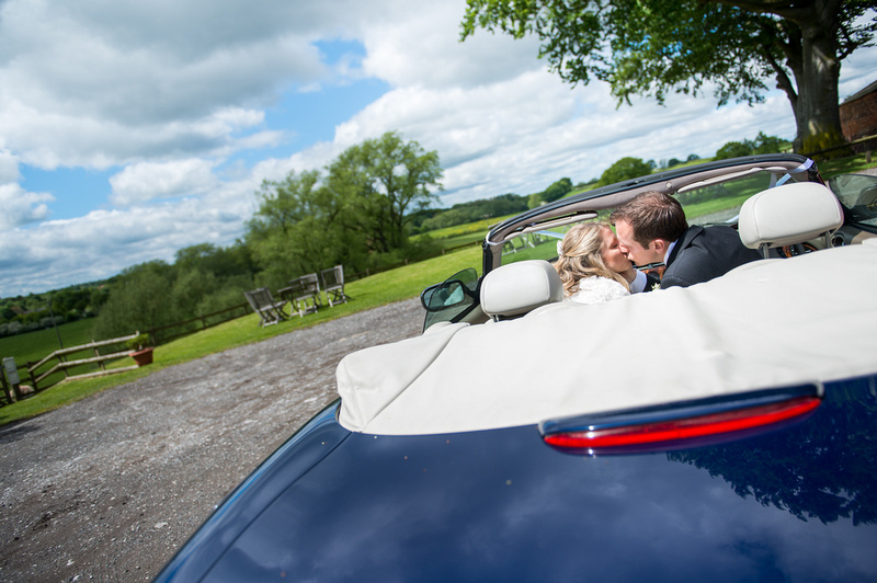 Photo of the bride and groom in a car kissing in Davenham.