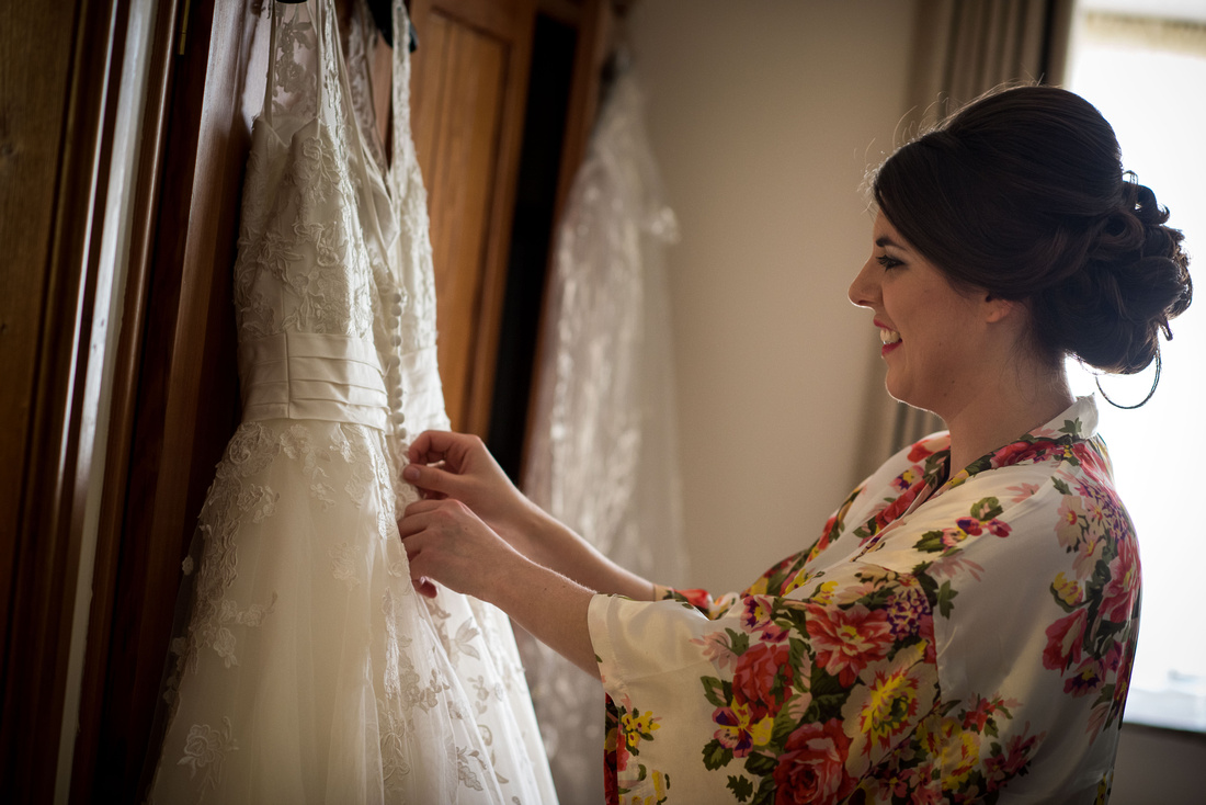Photograph of the bride admiring her wedding dress during bridal preparations before the wedding ceremony at Beeston Manor.