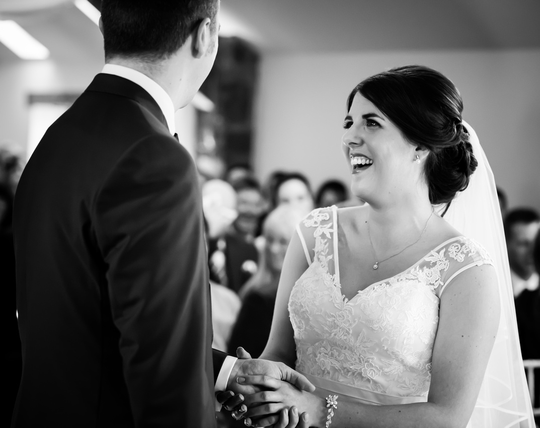 Black and white image of a bride enjoying standing next to her groom during their wedding ceremony at Beeston Manor.