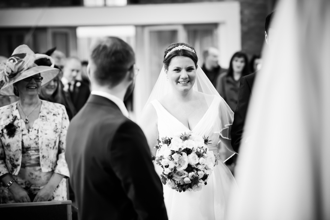 Black and white image of the bride smiling at her groom when she walks down the aisle.