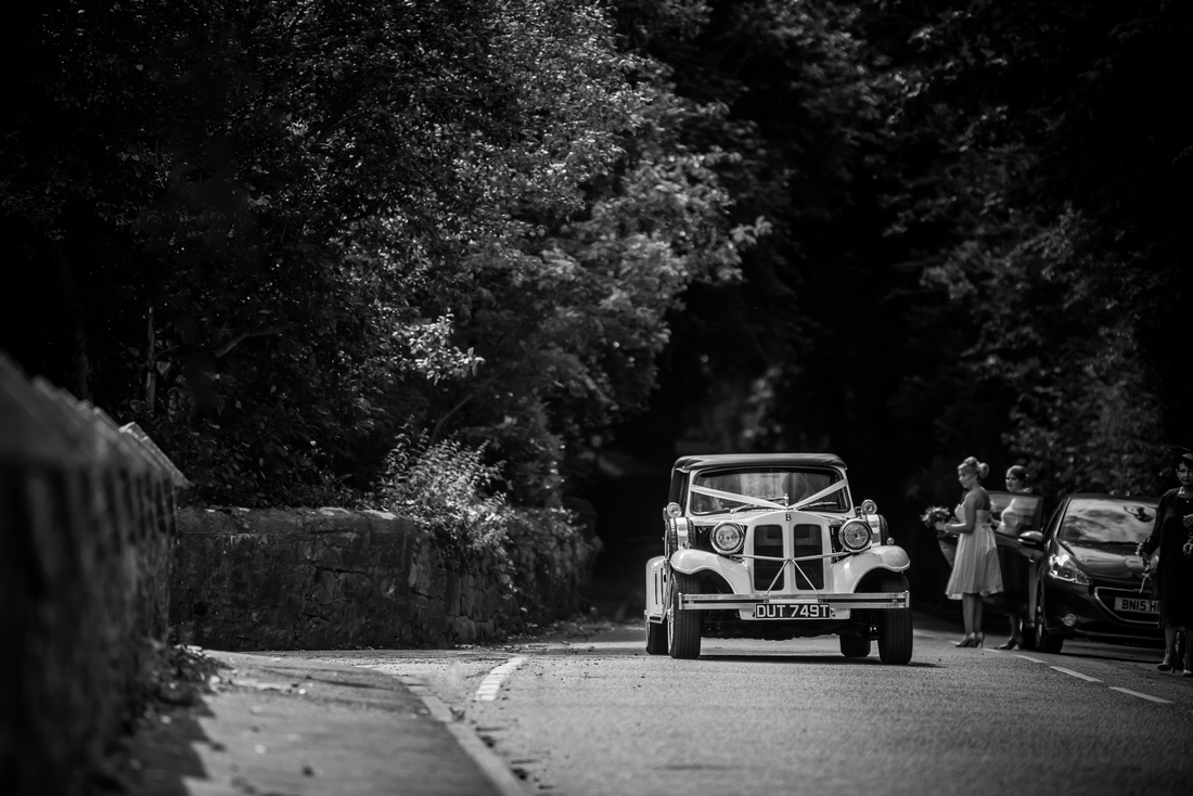 Black and white image of the bride arriving in a car at the church, in Halkyn, for the wedding ceremony.