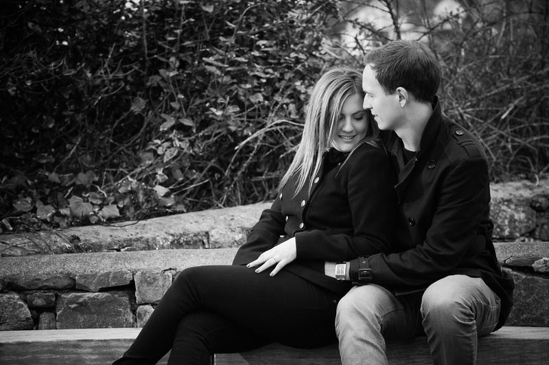 Black and white image of an engaged couple sitting on a bench together during their pre wedding shoot.