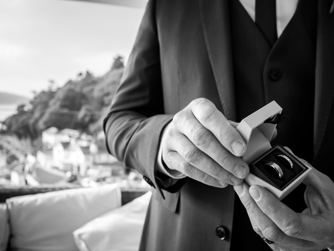 Black and white image of the best man holding the wedding rings before the ceremony at a wedding in Portmeirion.