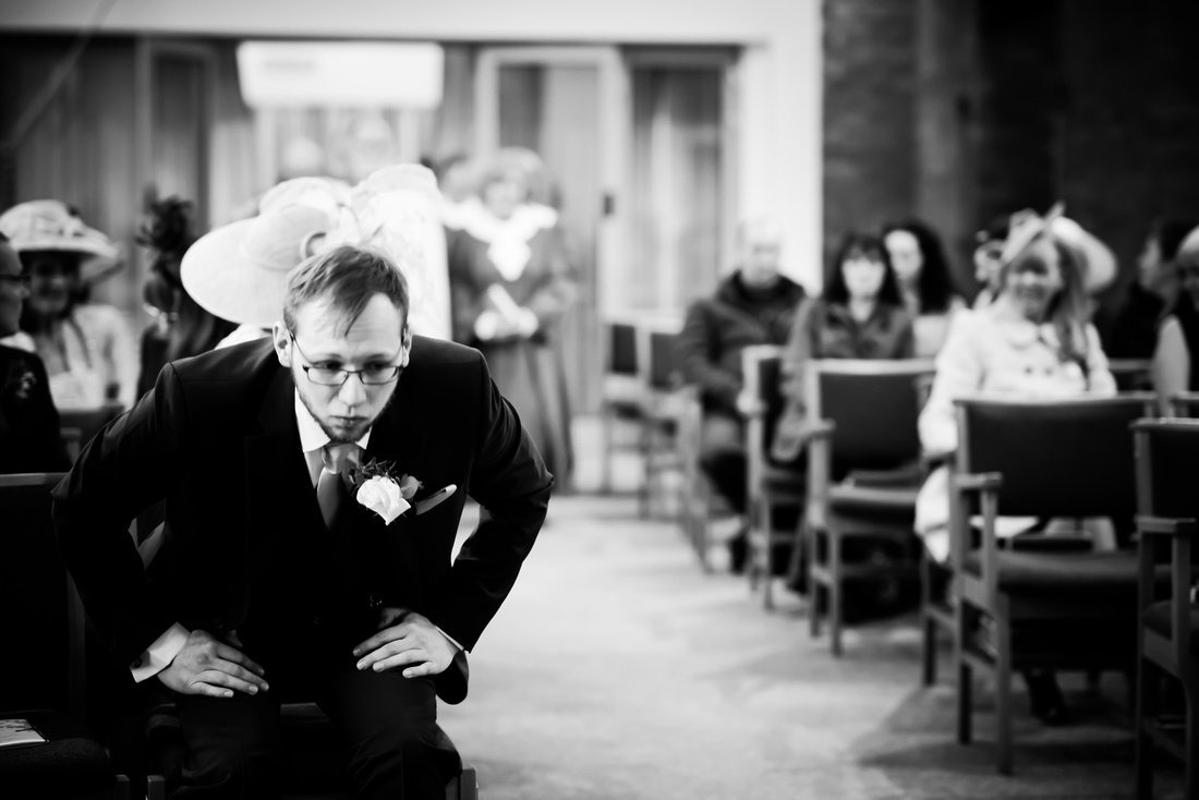 Black and white image of the groom preparing himself for the wedding ceremony.