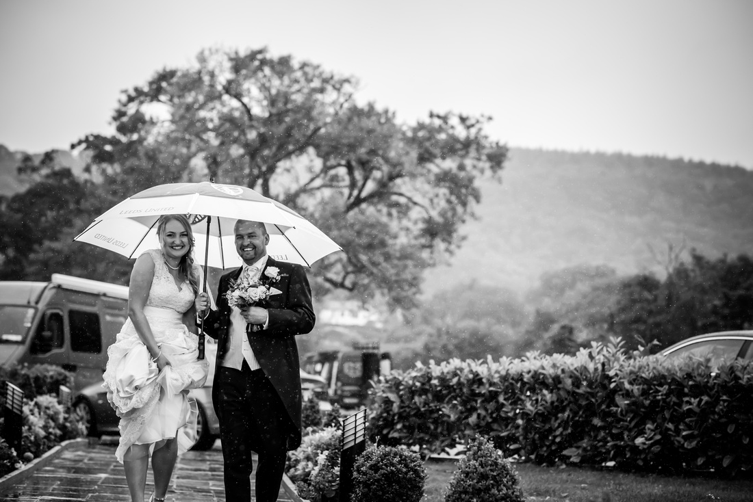 Black and White image of the bride and father arriving at the wedding venue, The Kinmel, on a rainy day.