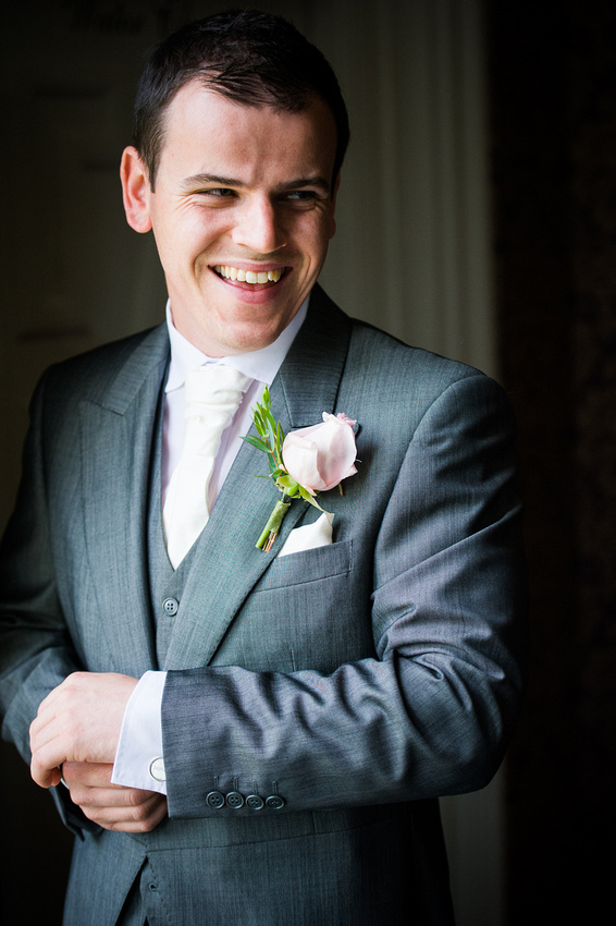 Groom, smiling at his best man at his wedding at Chateaux Rhianfa, Anglesey. Wedding Photographer, Celynnen Photography